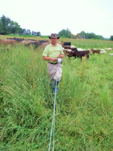 Farmer John Burns rolls up a line of fencing to let his flerd head to the next pasture. Photo by Troy Bishopp